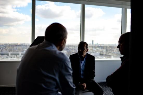illustrasjonsbilde uklare menn i dialog med utsikt gjennom vindu