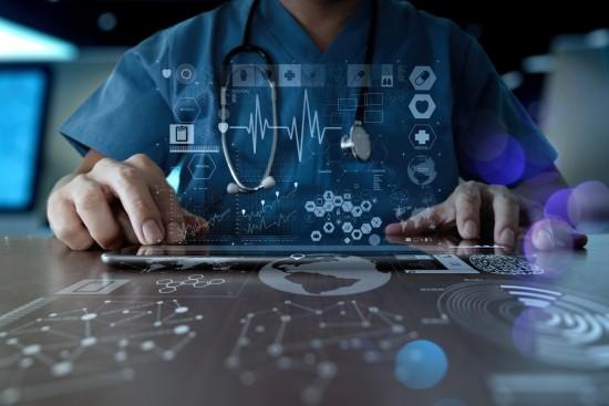 Sykehusansatt analyserer data på et skjermbrett.