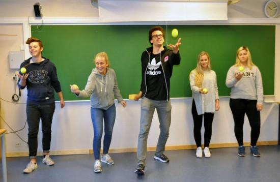 Fem elever kanster en tennisball i luften og fanger den igjen.