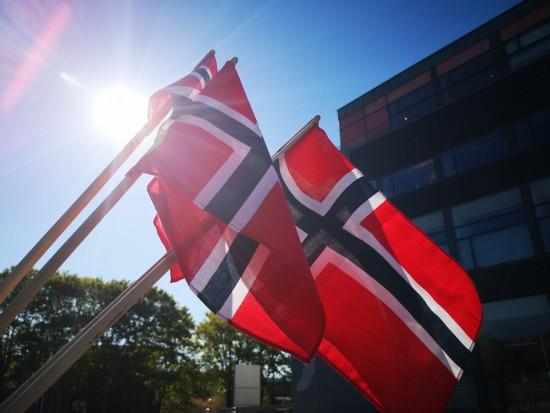Three norwegian flags seen from below. Blocking the sun.