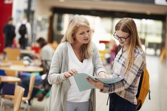En lærer og en elev ser i en bok sammen.