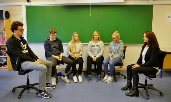Fem elever sitter sammen med Kjersti Tharaldsen i et klasserom. De har samlet stolene foran tavla, og sitter med lukkede øyne mens de øver på oppmerksomt nærvær.
