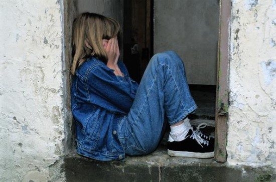 Jente som sitter sammenkrøpet i en døråpning med hendene foran ansiktet