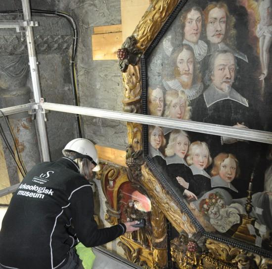 Malerikonservator undersøker Godtzenepitafiet før demontering