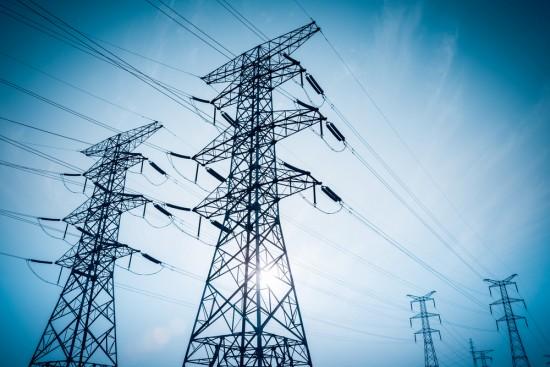 Foto av store master med strømnett i siluett med himmel bak.