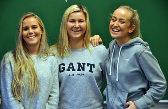 Tre blide jenter med armene rundt hverandre