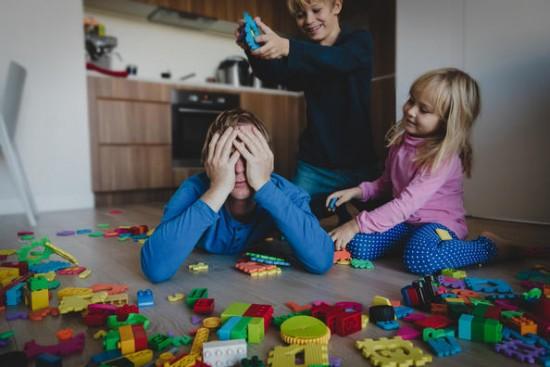 En far ligger på magen på gulvet med hendene foran ansiktet. To barn leker vilt rundt ham. Det er fullt av leker på gulvet.