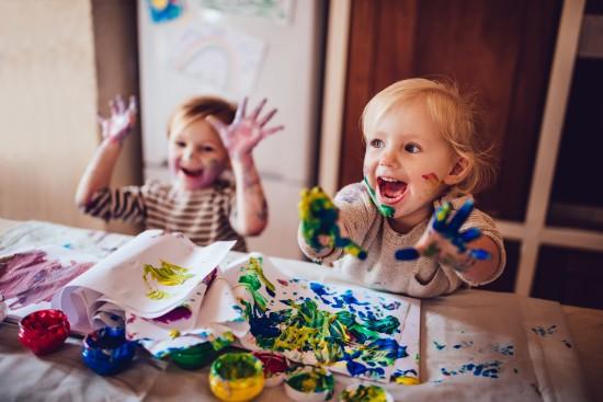 To smilende små barn maler med hendene