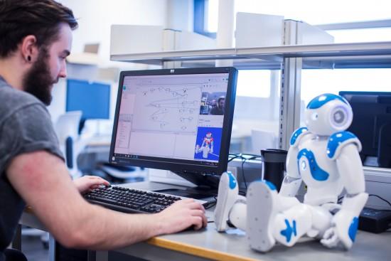 Student med PC og robot. Foto: Elisabeth Tønnesen