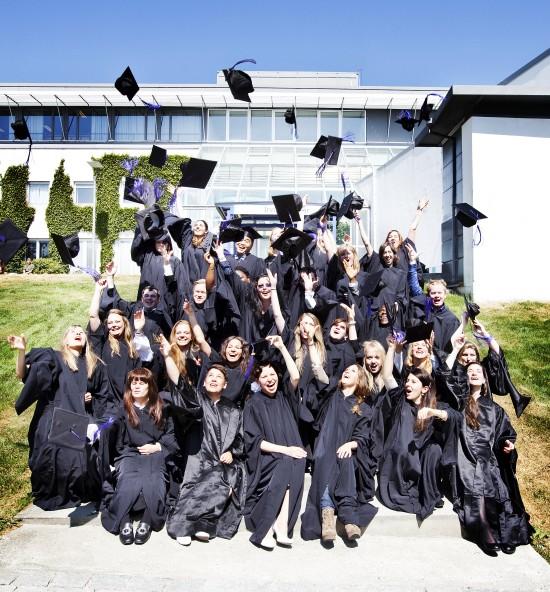 Alumner med hatter i luften