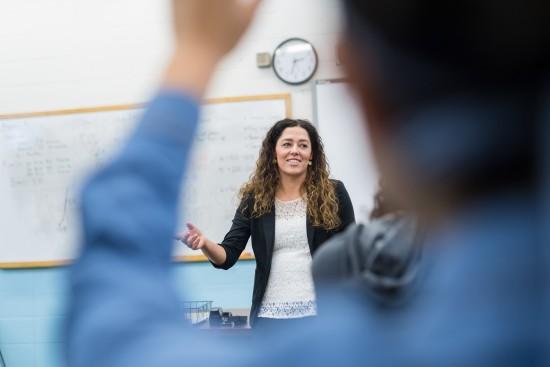 Kvinnelig lærer i klasserom og elev som rekker opp hånd
