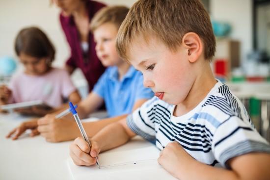 Skolebarn skriver og tegner i klasserom, lærer i bakgrunnen