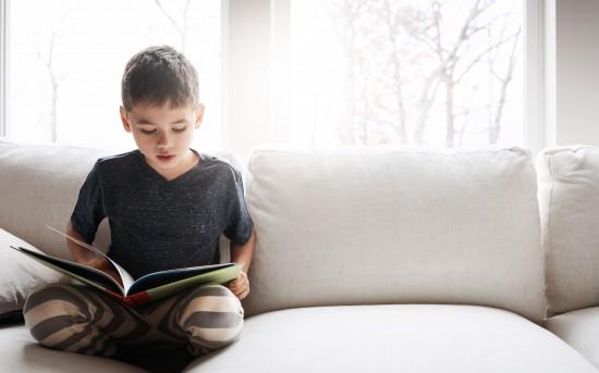 gutt leser i sofaen