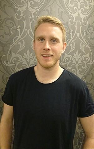 Mann med lyst hår og svart t-skjorte ser på kamera.