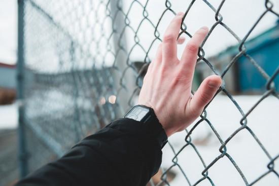 En hånd holder på et nettinggjerde.