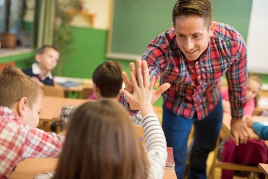 """Mannlig lærer gir """"high five"""" til en ung barneskoleelev i et klasserom"""
