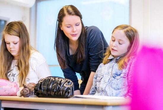 Lærer hjelper o barneskoleelever