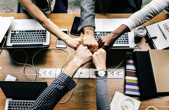 Fem knyttnever møtes i midten over et bord med datamaskiner, mobiler, notater og kaffekopper.