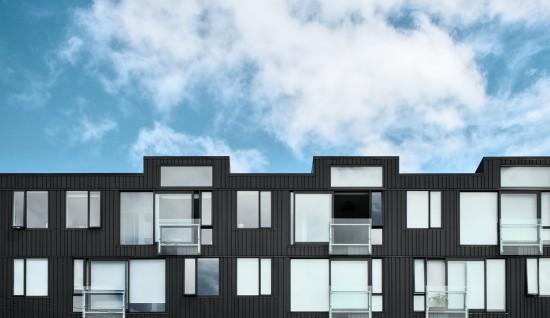 Moderne leilighetsbygg med store vinduer.