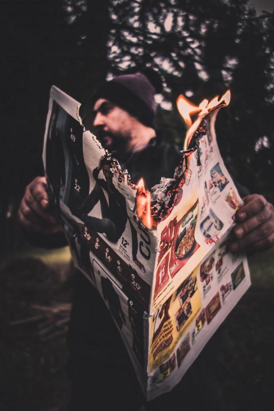 En mann med lue holder en åpen, brennende avis.