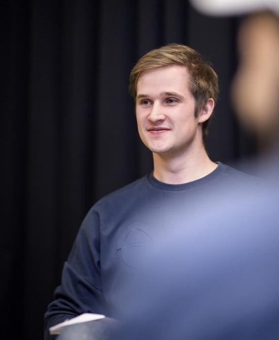 Ung mann med brunt hår og blå genser smiler