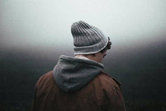 Bildet viser ryggen til en ung mann med grå lue, jakke og hettegenser.