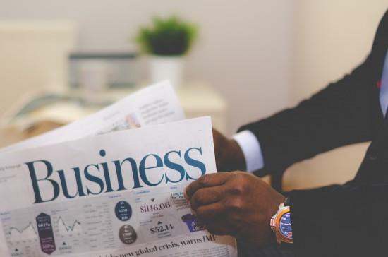A businessmann holding a business newspaper by Adeoli Eletu