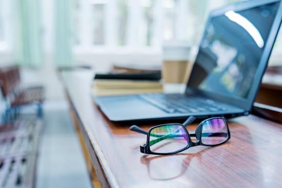 Bærbar pc og briller ligger på et bord.