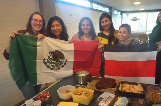 The master chefs for the class dinner, holding flags with food in front of them.