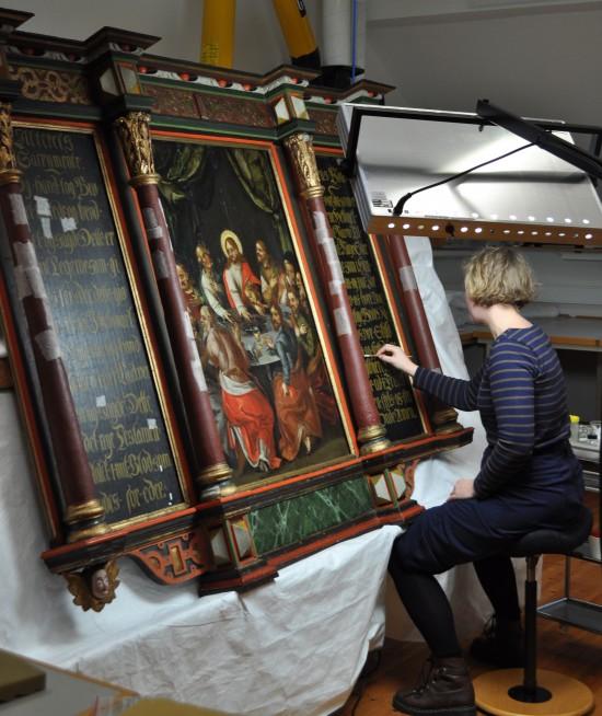 Malerikonserveringsstudent renser altertavlen fra Randaberg