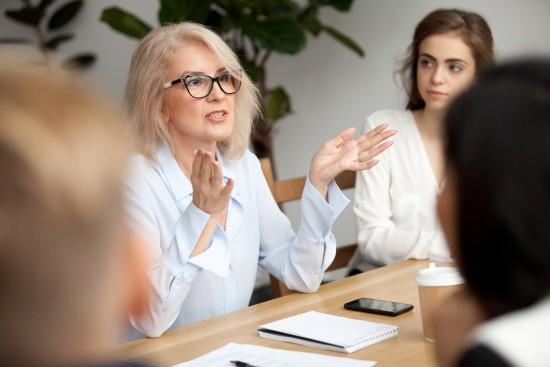 En kvinne sitter og snakker i et møte.