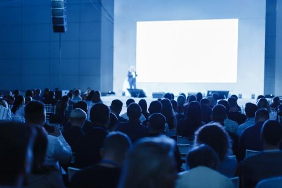 Foredragsholder på scene med full sal og blått lys