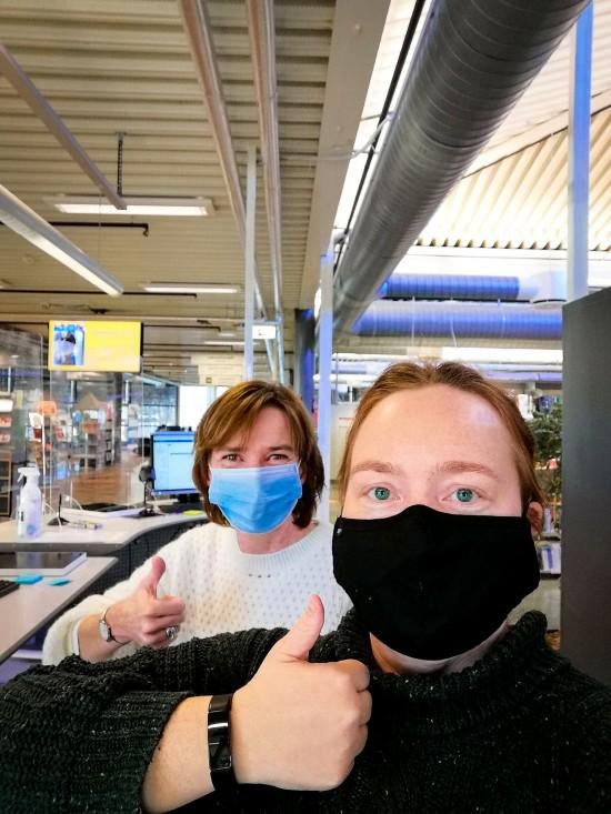 To kvinner med munnbind i biblioteket skranke