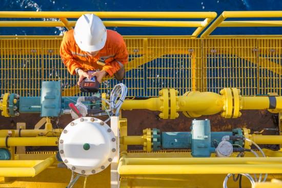 Flerkompetansebetjeningstekniker kalibrerer oljefeltet instrument, Coriolis flowmåler og aktuert styreventil på offshore olje- og gassplattform. Foto: Shutterstock