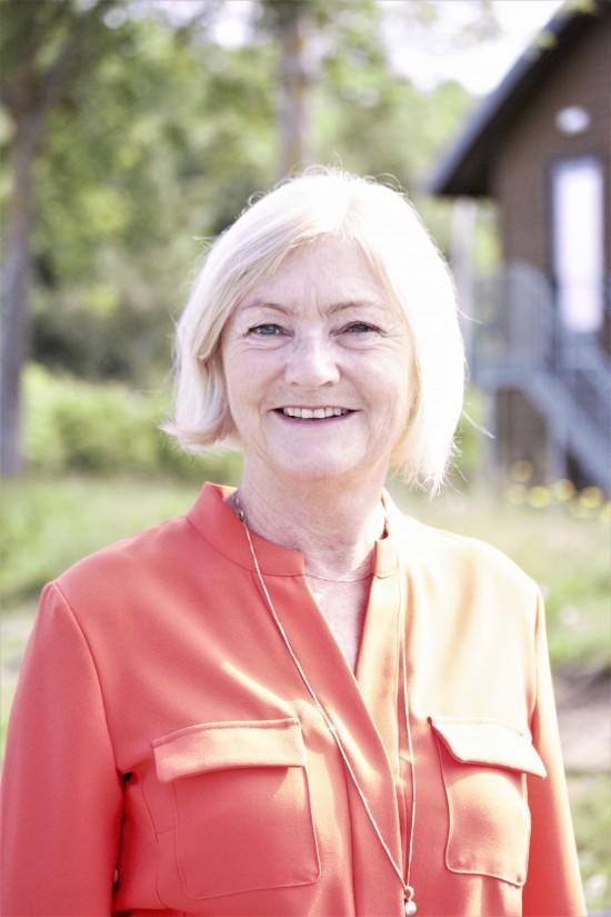 Smilende kvinne med rød skjørte og lyst hår