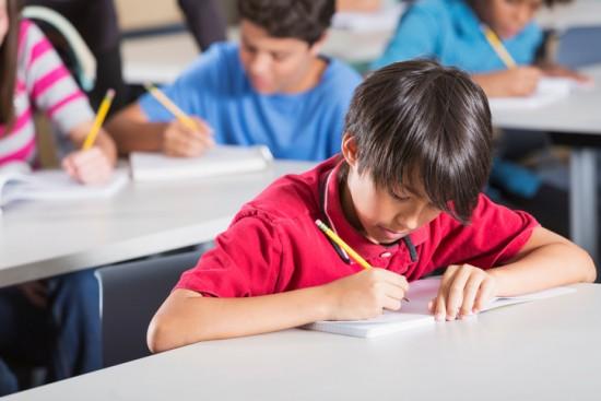 Gutt sitter ved en pult i et klasserom og skriver.