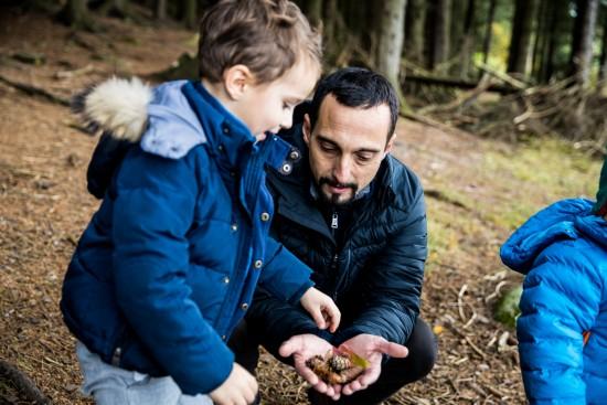 To barn og en voksen leker med kongler