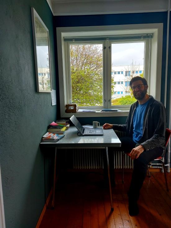 Sander Eriksen Mathisrud sit med ein open laptop ved eit kjøkkenbord. Han smiler mot kamera.