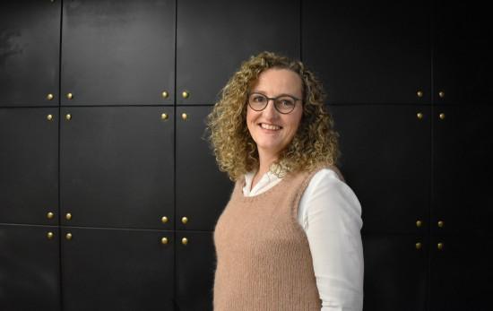Professor i barnevern og nettverksleder Ingunn T. Ellingsen. Hun og er iført en hvit skjorte med beige vest. Hun har briller og mørkeblondt krøllet hår, hun står vendt  til siden, vekk fra kameraet med kroppen og ser inn i kameraet. Bak henne er en mørk vegg med gulldetaljer.
