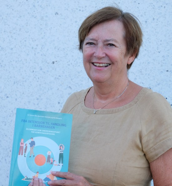 Elin Ødegård viser fram boka Fra intensjon til handling i barnehagen.