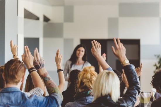 Et klasserom sett bakfra. Alle elevene har en hånd i været. Læreren skimtes foran i klasserommet.