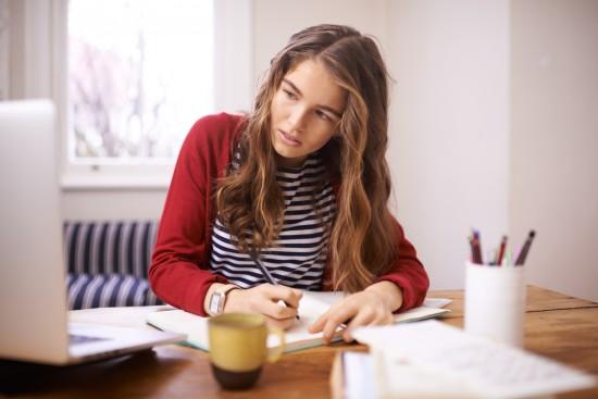 Jente som noterer i en bok mens hun ser på en skjerm