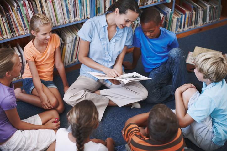 Kvinnelig lærer sitter på gulvet og leser sammen med en gruppe elever