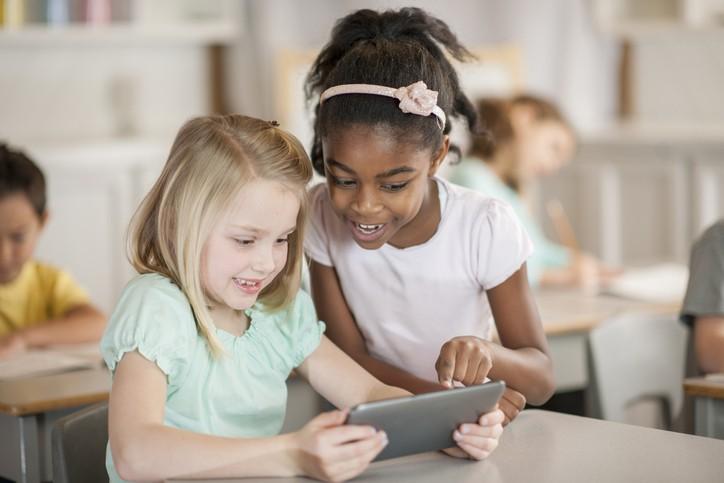 to jenter med nettbrett i klasserommet. foto: getty