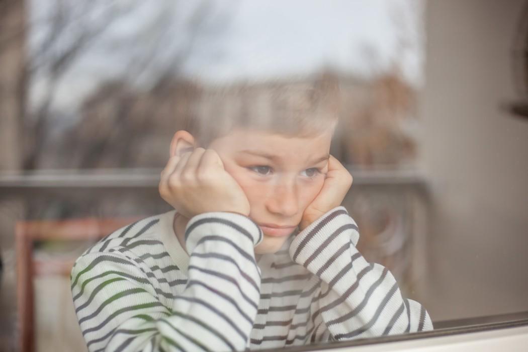 Gutt kikker ut gjennom et vindu.