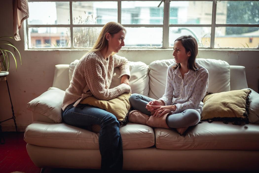 Voksen og barn snakker sammen i en sofa.