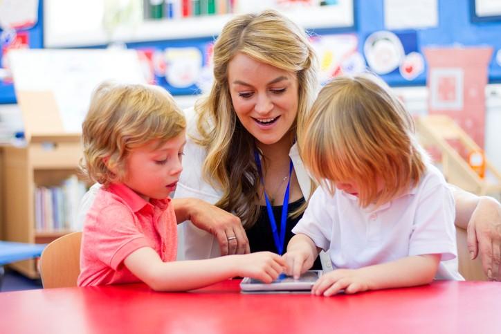 Barnehagelærer og to barn holder på med et nettbrett