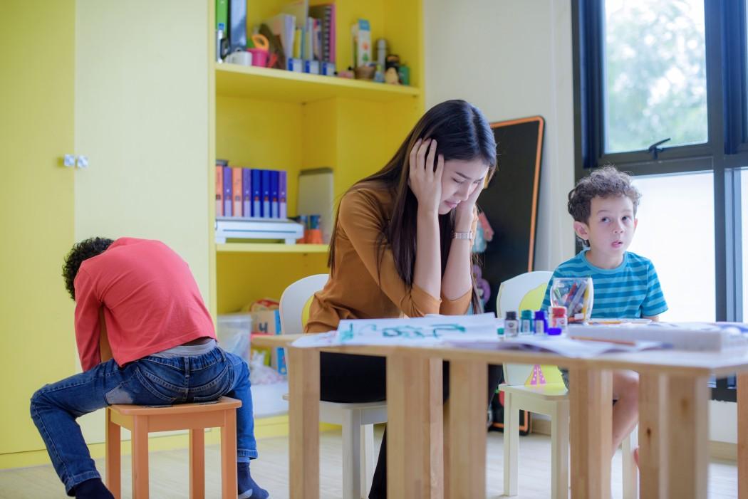 Mor og to barn sitter i samme rom. Alle virker oppgitte.