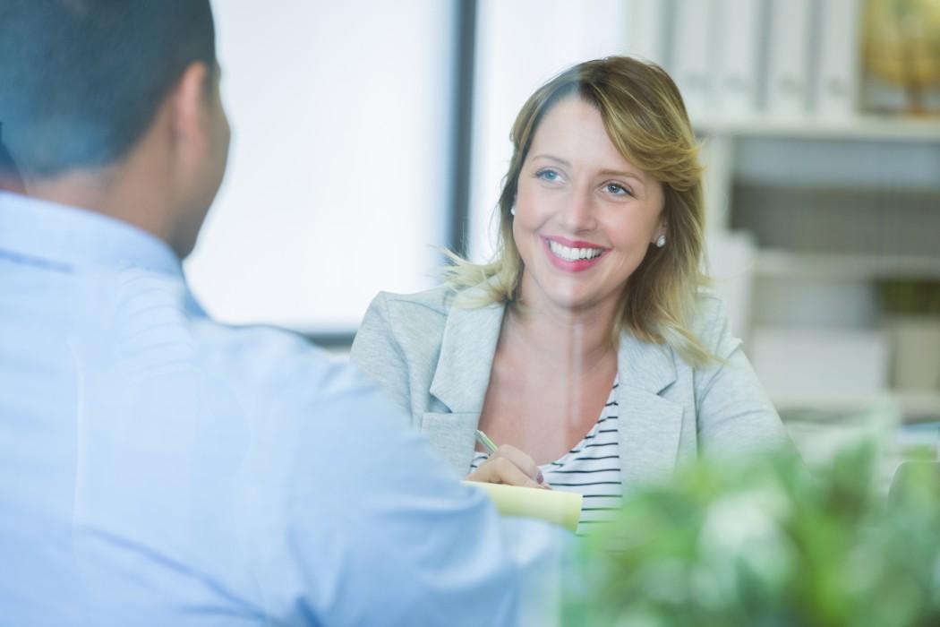 En dame og en mann snakker sammen.  Kontorhylle i bakgrunnen.