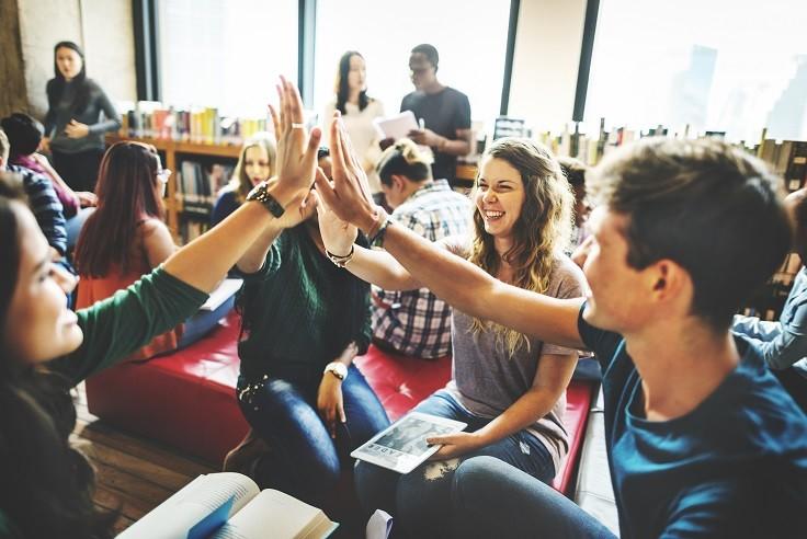 Flere ungdommer gir hverandre high five i et klasserom